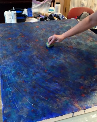 Artist Joanne Dvorsky demonstrates technique on a large canvas.