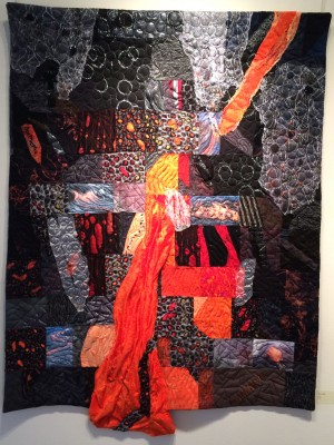"Shirley Moses' ""Lava"" has multiple layers of tactile fabric pieced, and in places stuffed, to add dimension and in places cut to show the bubbling ""heat"" within the volcano. Machine embroidery adds texture to emphasize the power, beauty and benefit of a volcano, and machine applique adds additional dimension with cascading lava relentlessly flooding the area beyond the volcano."
