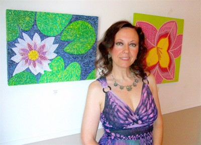 "Natalya B. Parris with her works, left ""The Bride,"" acrylic on canvas, white water lily flower; right ""Georgia,"" acrylic on canvas, enlarged pink flower inspired by Georgia Totto O'Keeffe."