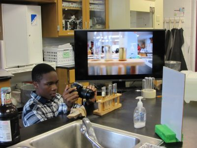 Freshman Tim Nwogu lines up a still shot for a Secret Society of Science Song-Writers (4SW) video at Northwest High School.