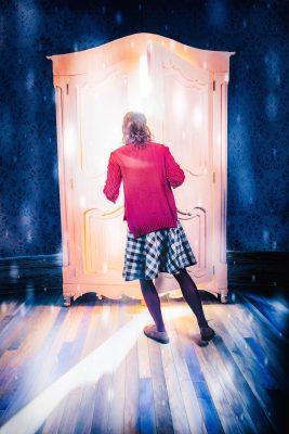 Lucy (Audrey Bertaux) enters Narnia through the magic wardrobe.