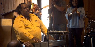 Grammy-winning musician Daryl Davis performs at the keyboard.