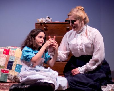 Anne Sullivan (Lena Winter) tries to teach Helen Keller (Meredith Abramson) how to spell with her fingers.