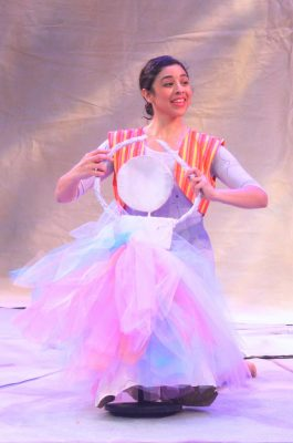 The dancer, Sara Herrera, plays with a paper doll ballerina.