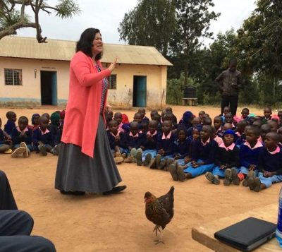 "During a school assembly in Wamunyu, Kenya, Ali Oliver-Krueger said, ""Yes, the chicken did just wander into the performance! That chicken had a lot of stage presence."""