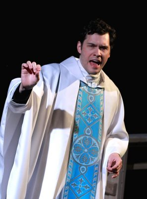 Father Flynn (Elliott Kashner) gives a sermon about gossip.