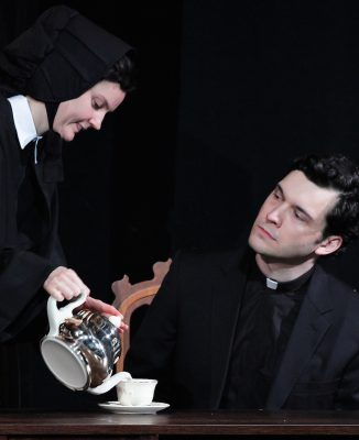 Sister James (Chelsea Mayo) pours tea for Father Flynn (Elliott Kashner).