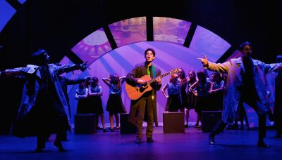 "Carlos Castillo, Pre-Professional alumnus, center stage playing the guitar in in ""Spotlight,"" the Pre-Professional program's annual showcase."
