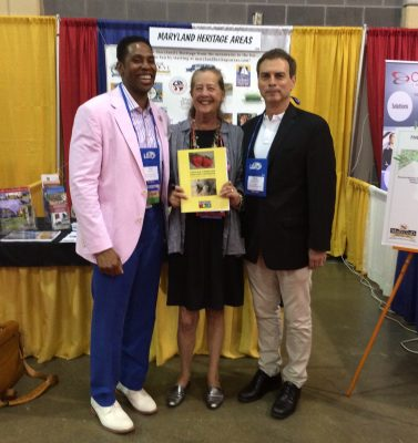 "From left, Montgomery County Councilmember Craig Rice, Heritage Montgomery Executive Director Sarah Rogers and District 15 State Senator Brian Feldman at the 2017 Maryland Association of Counties Conference display Heritage Montgomery's new ""African American Heritage Cookbook""."