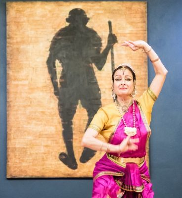 Bharatanatyam dancer Charu Narasimhan offered the dance invocation for Gandhi Jayanti for many years. Recently her senior dance students have begun to offer the invocation. This year, her student Asha Krishnakumar will offer the devotional dance. (The painting in the background is by Montgomery County artist Shanthi Chandarasekar.)