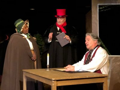"From left, Miriam Bowden and Peter Wolff, as Gentlewoman and Gentleman respectively, and Dino Coppa as Ebenezer Scrooge in Kensington Arts Theatre's ""A Christmas Carol."""