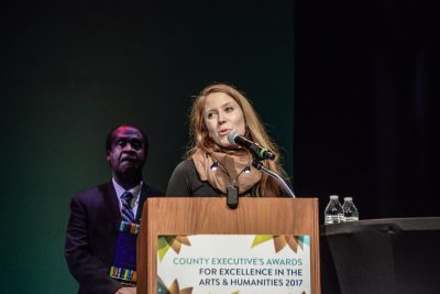 Cassie Meador speaks at the 2017 County Executive's Awards ceremony, with County Executive Isiah Leggett in the background.