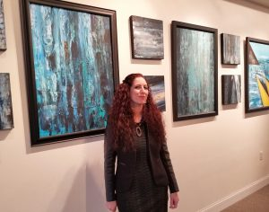 Vian Borchert in front of a wall of her work at The Framer's Choice Gallery in the Kentlands.
