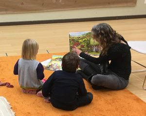 Two tots are fully engaged by a story told by World Story Time leader Jo Rasi.
