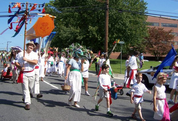 The Washington Revels, dressed in white with multicolored sashes and arm ribbons along with a Smiling Sun, will return to add their voices to the 51st annual Kensington Labor Day Parade.