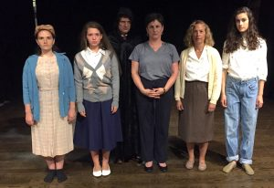 "The cast of Sandy Spring Theatre Group's ""Kindertransport,"" from left, features Becca Sears as Helga, Sophia Anthony as Eva, Mara Bayewitz as Evelyn, Jill Goodrich as Lil and Leah Packer as Faith. In the rear is John Van Eck as the Ratcatcher."