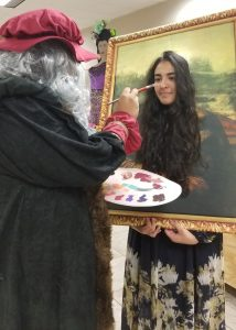 "Leonard DaVinci (Moisés Manilla) paints the ""Mona Lisa"" (Daniella Jaray)."
