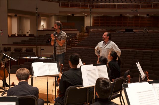 Brothers Kristofer and Rolando Sanz talk to musicians during a rehearsal.