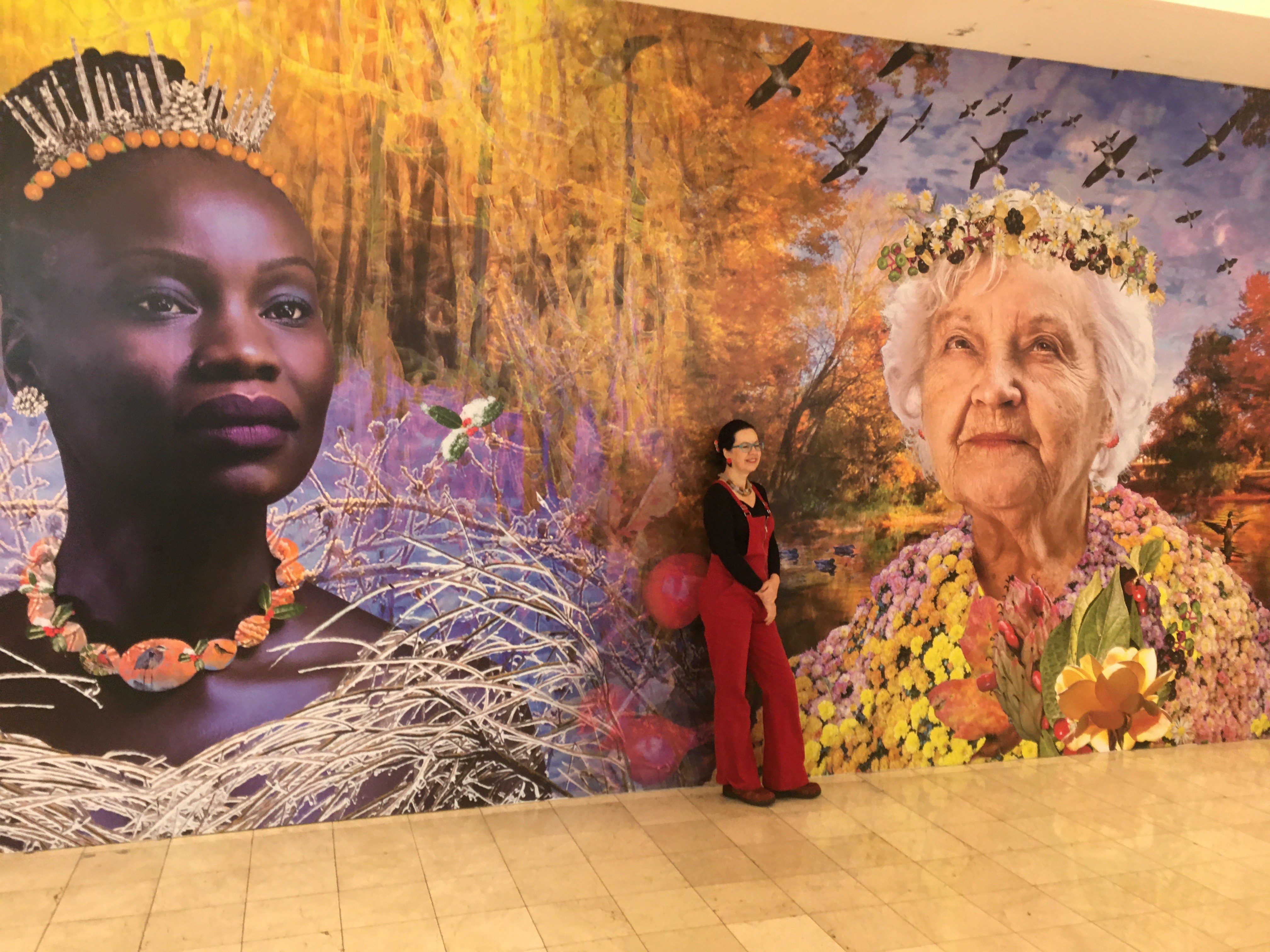 Liliane Blom stands before her mural in the mall.